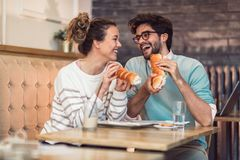 Cute young couple having a good time together and eating food in cafe. Cute young couple having a good time together and eating food in a coffee shop royalty free stock image