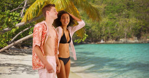 Cute young couple holding hands on tropical beach. Stock Photos