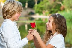 Cute young couple holding on to rose. Royalty Free Stock Photography