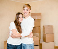 Cute young couple hugging on a background of cardboard boxes Royalty Free Stock Photography