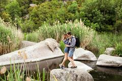 Cute couple hugging on stone in middle of river. Camping season stock image
