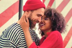 Cute young couple laughing while standing and hugging. Nice joke. Cheerful young curly women hugging her attractive bearded boyfriend and laughing at the funny stock photography