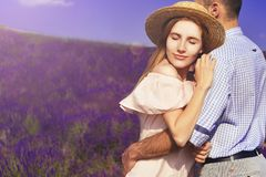 Young man holds woman in lavender field, cute young couple in love walking in a field of lavender flowers. Girl raises her hat up stock photography