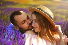 Cute young couple in love in a field of lavender flowers. Enjoy a moment of happiness and love in a lavender field. kiss stock photos