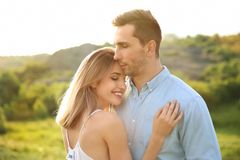 Cute young couple posing outdoors on sunny day. Cute young couple in love posing outdoors on sunny day Stock Photography