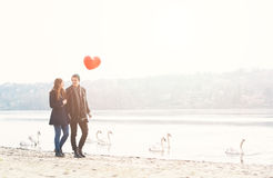 Cute young couple in love, walking at the riverside, with a red balloon Stock Image