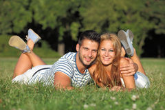 Cute young couple lying in a park Royalty Free Stock Image
