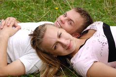 Cute young couple outdoor. Young couple laying on the grass Stock Photo