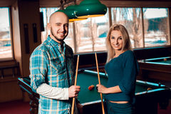 Cute young couple plays billiard and having some fun. American pool billiard. Billiard sport concept. Pool billiard game stock photos