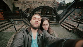 Cute young couple is posing for a selfie in the courtyard of an old castle stock video footage