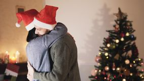 Cute young couple in Santa hats dancing and hugging in the room in front of the Christmas tree. New Year and Christmas. Young positive couple in Santa hats stock video footage