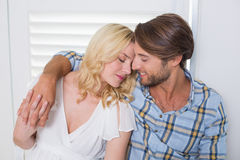 Cute young couple sitting on floor together holding hands Stock Images