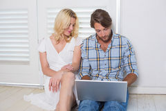 Cute young couple sitting on floor using laptop Stock Photography