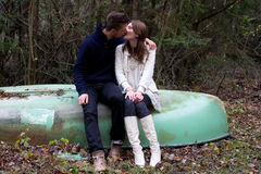 A cute young couple sitting on a old boat. And kissing Stock Photo