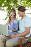 Cute young couple sitting on park bench using laptop Royalty Free Stock Image
