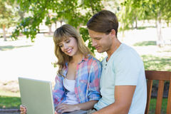 Cute young couple sitting on park bench using laptop Stock Photo