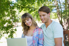 Cute young couple sitting on park bench using laptop Stock Images