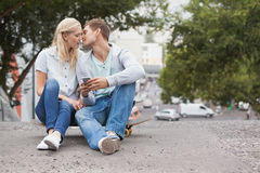 Cute young couple sitting on skateboard kissing Stock Photography