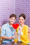 Cute young couple sitting at the table holding a heart Stock Images