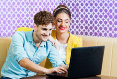 Cute young couple sitting at the table with laptop Royalty Free Stock Images