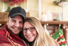 Cute young couple snuggled up in winter. Cute young couple snuggling up in a blanket in wintertime Royalty Free Stock Image