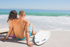 Cute young couple with their surfboards looking at the sea. Cute young couple on the beach with their surfboards looking at the sea Royalty Free Stock Photos
