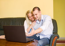 Cute young couple using net thru laptop. Stock Photos