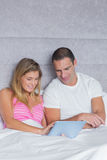 Cute young couple using their tablet pc together in bed Stock Images