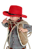 Cute young cowboy toddler biting a rope wearing re Stock Images