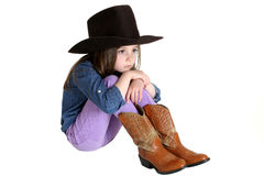 Cute young cowgirl sitting with her knees up Stock Photography