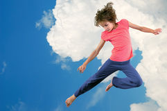 Cute young dancer girl jumping against bue sky. Portrait of cute young dancer girl against blue cloudy sky. Horizontal royalty free stock photo