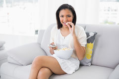 Cute young dark haired woman in white clothes eating popcorn while watching tv Royalty Free Stock Photography