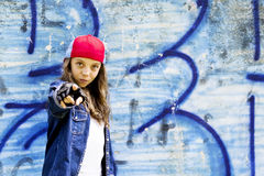 Cute young fair-haired girl teenager in a baseball cap and denim shirt on a stone wall background. Stock Photography