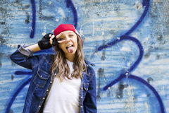 Cute young fair-haired girl teenager in a baseball cap and denim shirt on a stone wall background. Stock Photo