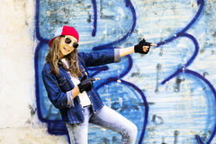 Cute young fair-haired girl teenager in a baseball cap and denim shirt on a stone wall background. Hip hop, dancing Stock Photos
