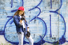 Cute young fair-haired girl teenager in a baseball cap and denim shirt on a stone wall background. Hip hop, dancing Royalty Free Stock Photo