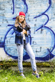 Cute young fair-haired girl teenager in a baseball cap and denim shirt on a stone wall background. Hip hop, dancing Royalty Free Stock Photos