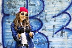 Cute young fair-haired girl teenager in a baseball cap and denim shirt on a stone wall background. Hip hop, dancing Royalty Free Stock Images