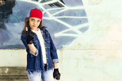 Cute young fair-haired girl teenager in a baseball cap and denim shirt on a stone wall background. Hip hop, dancing Royalty Free Stock Image
