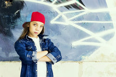 Cute young fair-haired girl teenager in a baseball cap and denim shirt on a stone wall background. Hip hop, dancing Stock Photo