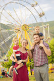 Cute young family enjoying a day at amusement park. Happy young family enjoying a day at amusement park having fun on the carnival rides. Large Ferris wheel in Royalty Free Stock Image