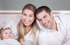 Cute young family at home Stock Images