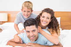 Cute young family smiling at camera on bed posing Royalty Free Stock Images