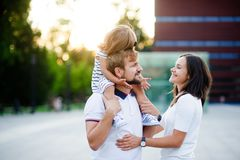 Cute young family on a summer day in the city square. Man holds a small daughter on his shoulders. Woman is hugging her husband. She looks with love and Stock Photography