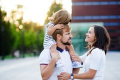 Cute young family on a summer day in the city square. Man holds a small daughter on his shoulders. Woman is hugging her husband. She looks with love and Royalty Free Stock Image