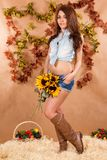 Cute young farmer girl holding the sunflowers Royalty Free Stock Image