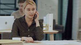 Cute young female adult on phone while working at desk stock footage