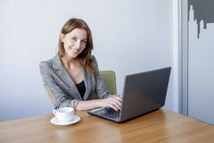 Cute young female adult working on laptop computer at desk next to coffee cup Royalty Free Stock Images