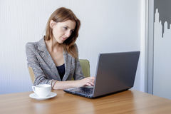 Cute young female adult working on laptop computer at desk next to coffee cup Royalty Free Stock Photos
