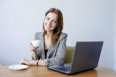 Cute young female adult working on laptop computer at desk next to coffee cup Royalty Free Stock Photo